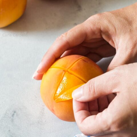 Peeling a peach with hands