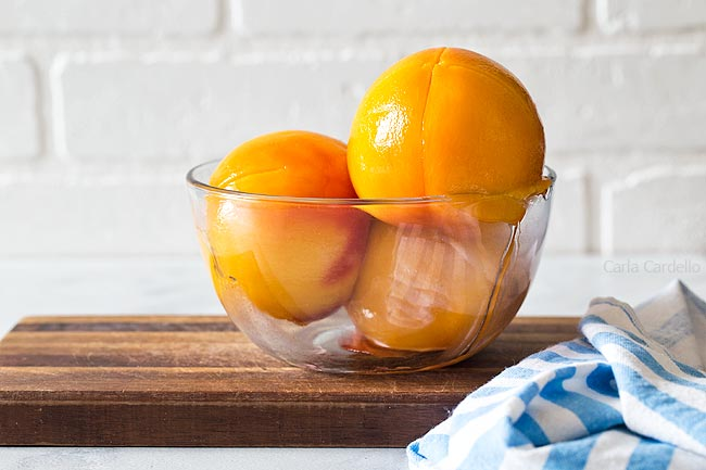 Glass bowl with 3 peeled peaches