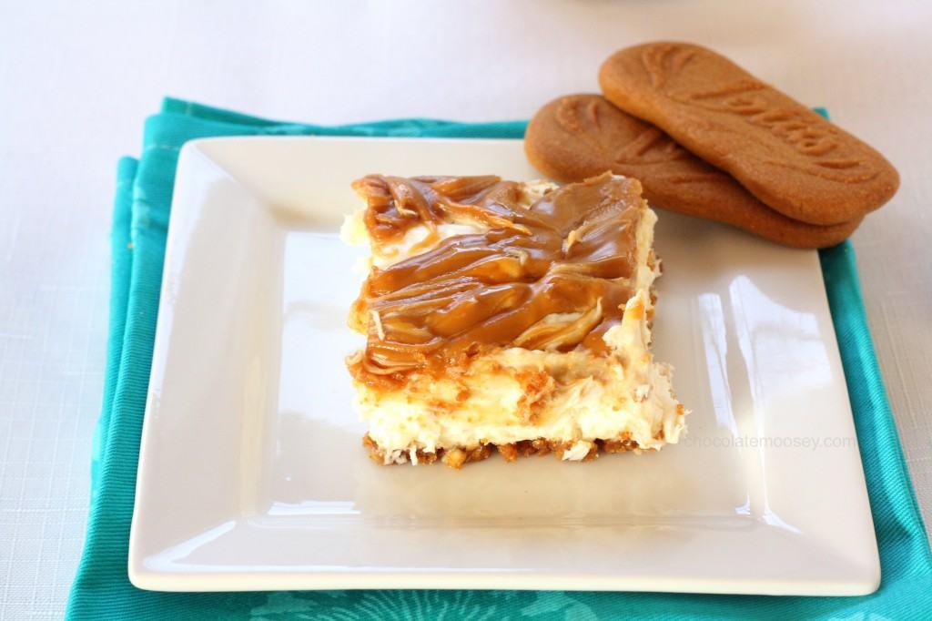 overhead shot of slice of biscoff cheesecake with 2 cookies on a white plate