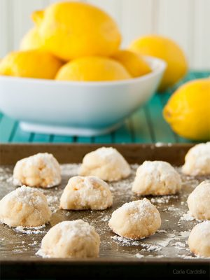 Easy melt-in-your-mouth lemon snowball cookies tossed in powdered sugar are a burst of lemon flavor with a bit of crunch from lemon chocolate chips.