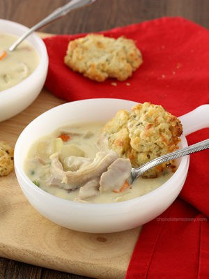 Craving chicken pot pie for two but don't have time to make it? This Chicken Pot Pie Soup recipe with cheddar biscuits has all of your favorite ingredients in one bite without having to make a pie crust.