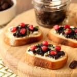 Raisin Jam and Goat Cheese Crostini with pomegranate seeds and fresh basil