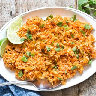 Spanish Rice on white platter with lime slices