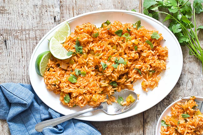 White platter of Spanish rice with spoon and small plate