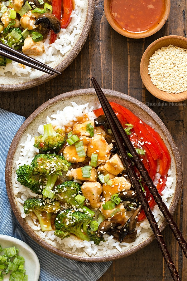 A cheaper and healthier alternative to Chinese takeout - homemade General Tso's Sweet Chili Chicken Rice Bowls with broccoli, red bell pepper, and mushrooms.