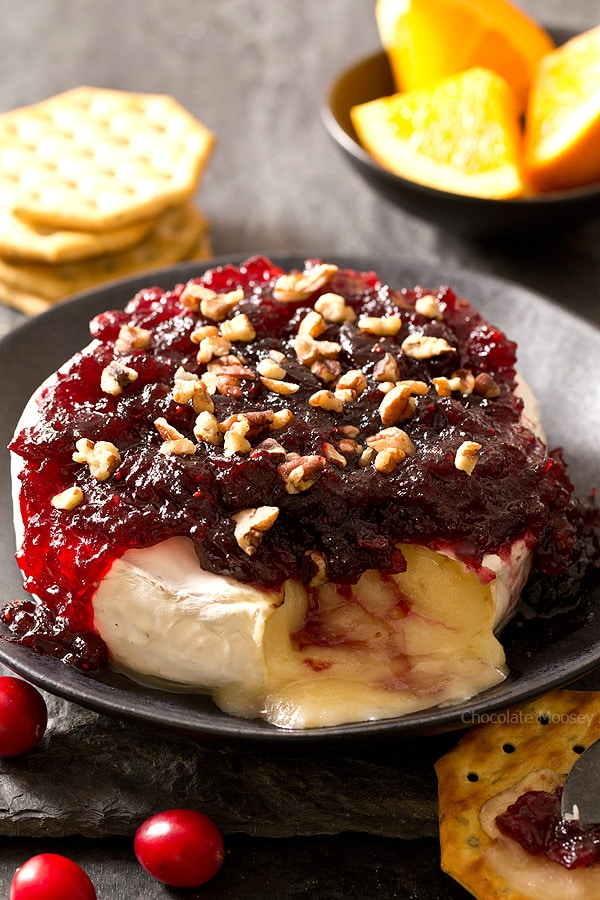 The easiest snack you can make for entertaining holiday guests - Cranberry Baked Brie served on a festive cheese board with crackers and fruit. Ooey gooey cheese ready in 10 minutes!