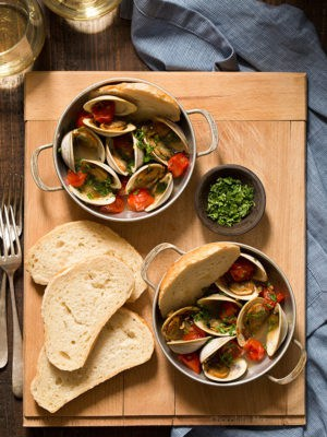Learn how to make Steamed Clams with Pan Roasted Tomatoes as an easy date night appetizer to make at home! This recipe makes enough to serve two people, ideal for Valentine's Day, anniversaries, birthdays, and days off together.