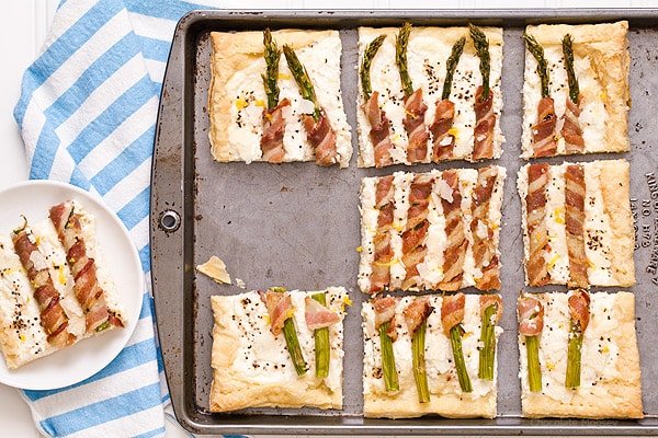 Bacon Wrapped Asparagus Puff Pastry Tart with a Parmesan ricotta cheese filling is a delicate, flakey appetizer to celebrate spring and Easter. Serve it for brunch or dinner.