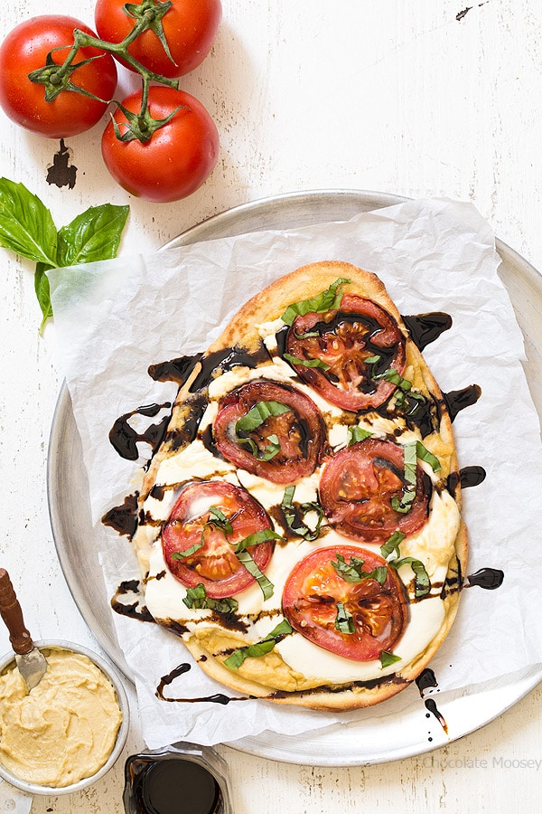 Caprese Hummus Flatbread Pizza with fresh tomatoes, sliced mozzarella cheese, basil, and balsamic vinegar