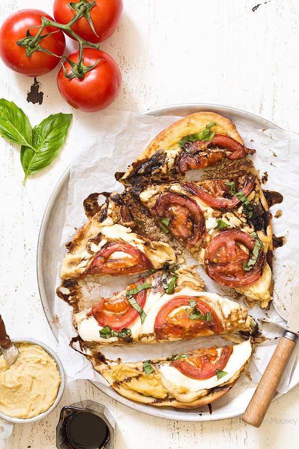 Looking for something quick and fresh to eat? Try this Caprese Hummus Flatbread Pizza with fresh tomatoes, sliced mozzarella cheese, basil, and balsamic vinegar.