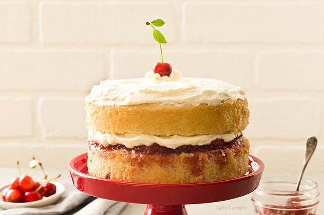a two layer vanilla cake recipe with a homemade sour cherry jam filling in the middle then topped with whipped cream from scratch.