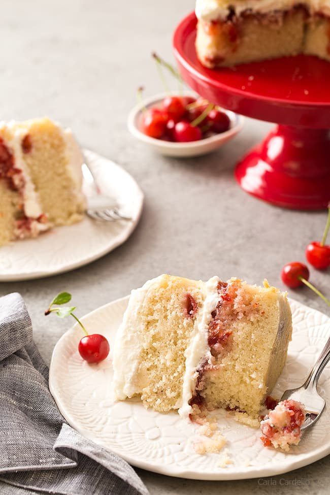 Slice of Cherry Vanilla Layer Cake with a cherry filling in between two layers of vanilla cake from scratch