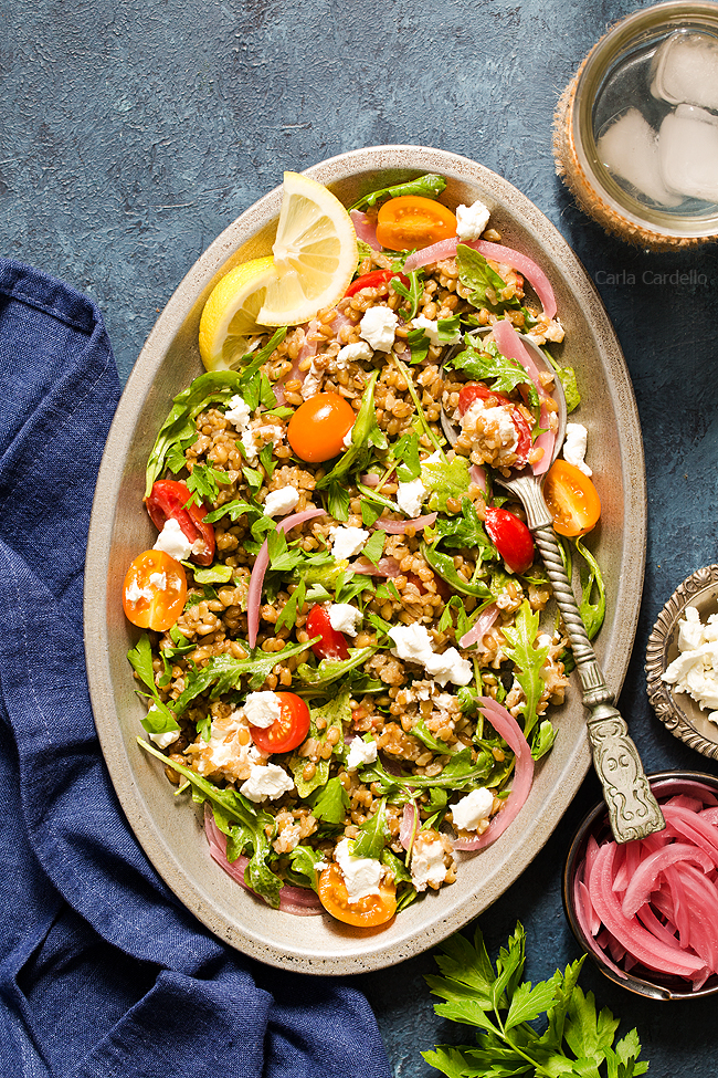 A hearty whole grain salad with freekeh, arugula, tomatoes, goat cheese, and pickled red onion.