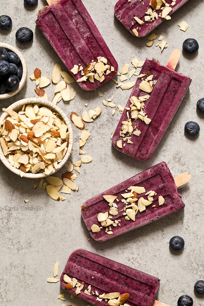 Cool down this summer with something colorful and refreshing! Blueberry Yogurt Popsicles with almonds and a secret ingredient that makes their flavor pop.