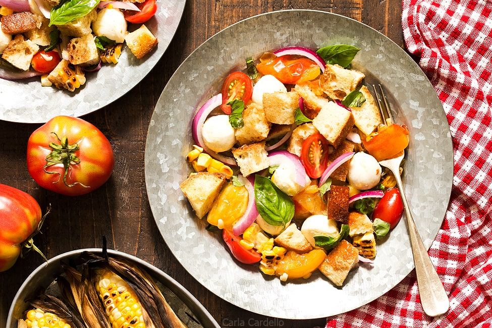Say hello to summer on a plate! Grilled Corn Panzanella Salad with tomatoes, mozzarella cheese, basil, and homemade croutons.