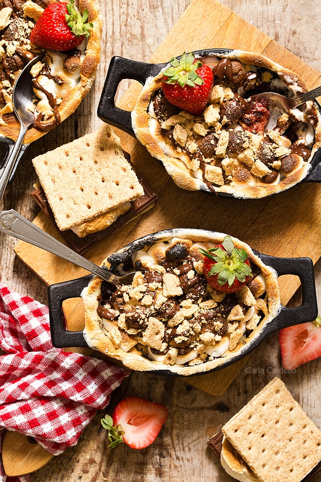No campfire needed for Strawberry S'mores Cobbler with a chocolate strawberry filling topped with toasted marshmallows and graham cracker pieces. Bake them in the oven for a gooey, irresistible smores dessert!