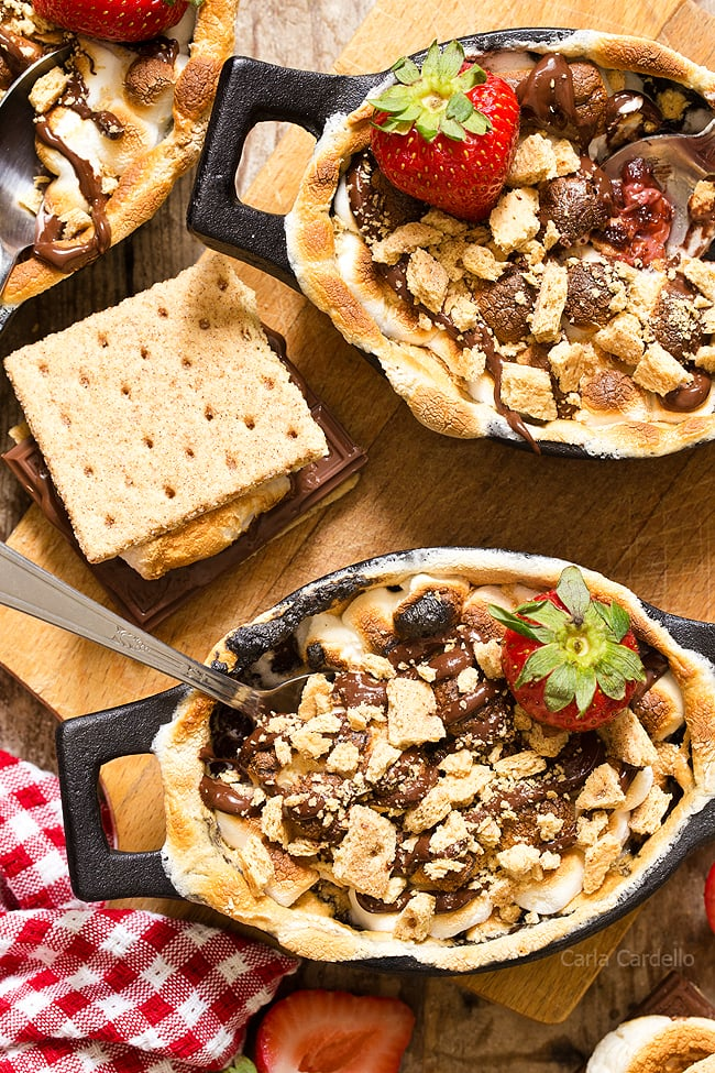 Strawberry S'mores Cobbler with a chocolate strawberry filling topped with toasted marshmallows and graham cracker pieces. Bake them in the oven for a gooey, irresistible smores dessert!