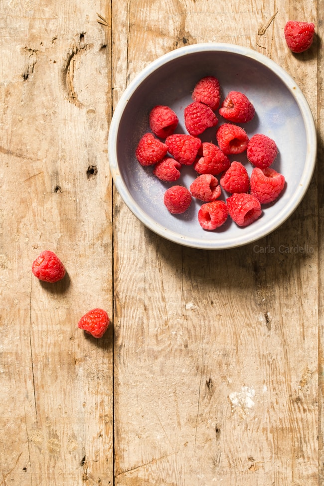 Bowl Of Raspberries On Rustic Wood