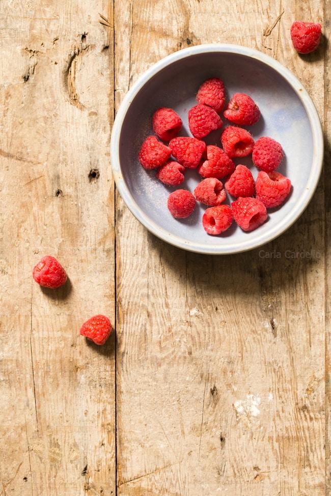 Bowl Of Raspberries On Rustic Wood