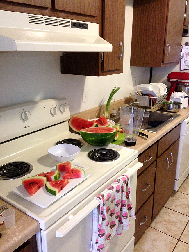 Cutting up watermelon in a small kitchen