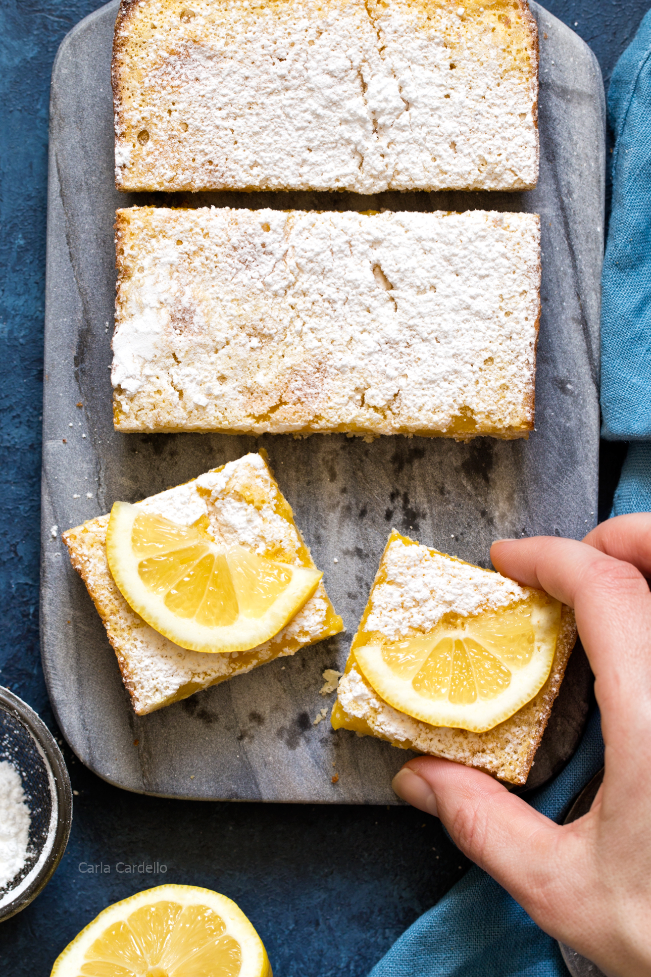 Hand grabbing Small Batch Lemon Bars made in a loaf pan