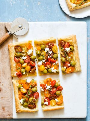 Celebrate the flavors of summer with Olive Tomato Puff Pastry Tart topped with goat cheese, thyme, and pine nuts.