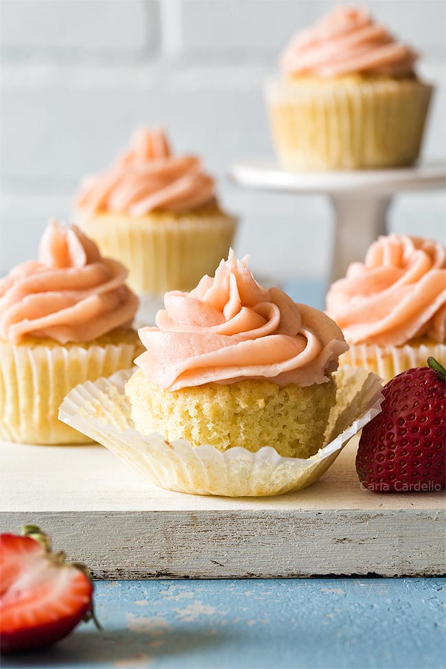 Group of vanilla cupcakes on white cutting board