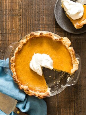 Small Pumpkin Pie in glass dish with slice missing